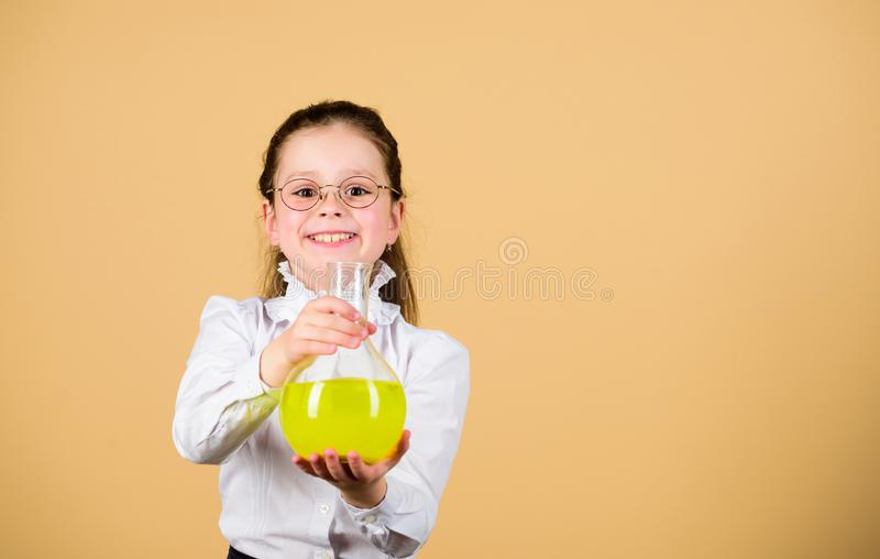 Small smart girl with testing flask. education and knowledge. child study bilogy lesson. science research in lab. Small. School girl. back to school. copy space royalty free stock image