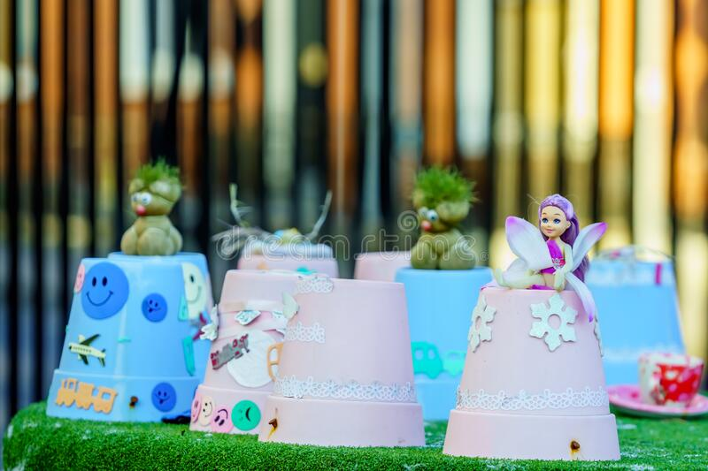 Small smiling fairy with wings and green trolls sitting on flower pots. Selective focus and blurred background royalty free stock photography