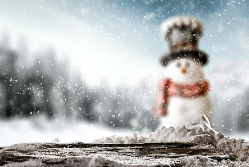 Small smiling snowman in a hat and scarf with white snowy winter background. Space for decorations on christmas background. stock photos