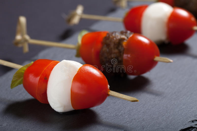Small snacks canape with cherry tomatoes, mozzarella and meatbolls on skewer on a black slate plate. Shallow depth of field.  royalty free stock image