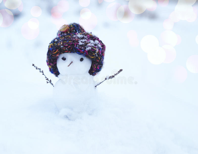 Small snowman in a knitted cap on snow in the winter. Festive background with a lovely snowman. royalty free stock image