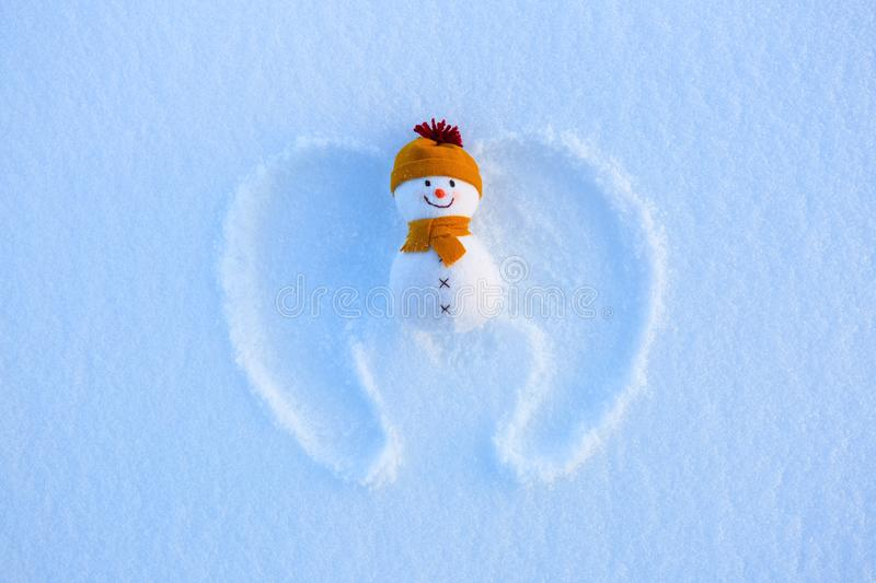 Small snowman puppet smiling with the hat and scarf and drawn angel wings. Happy new year. royalty free stock image