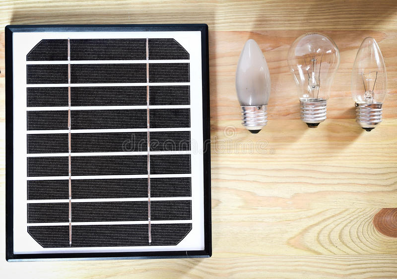 Small solar panel and three incandescent bulbs on the wooden table with copyspace, green energy abstract royalty free stock photos
