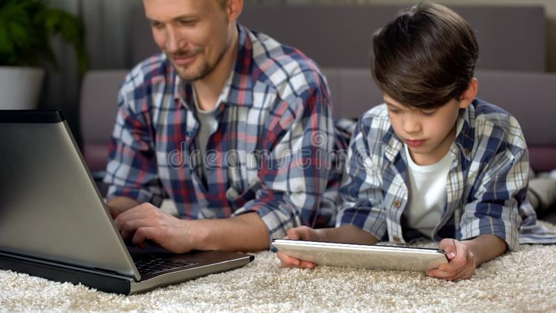 Small son playing on tablet on the floor at home while dad working on laptop royalty free stock images