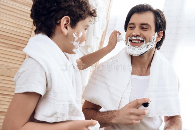 Small son smears father`s face with shaving foam. Family traditions concept stock photo