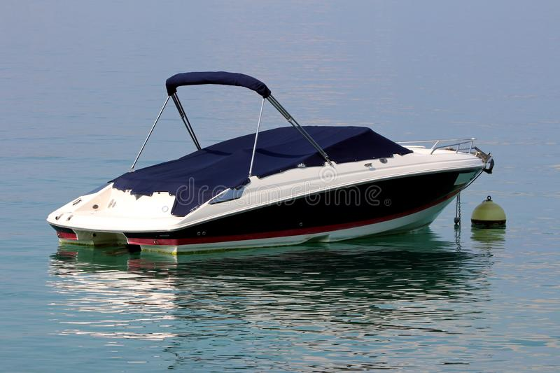 Small speed boat covered with dark blue protection anchored in local harbor surrounded with calm clear blue sea. On warm sunny summer day stock photography