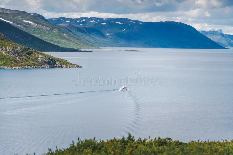 Small speed boat leaves traces on the water in the lake in Jotunheimen national park, traveling to Norway. Small speed boat leaves traces on the water in the royalty free stock photos