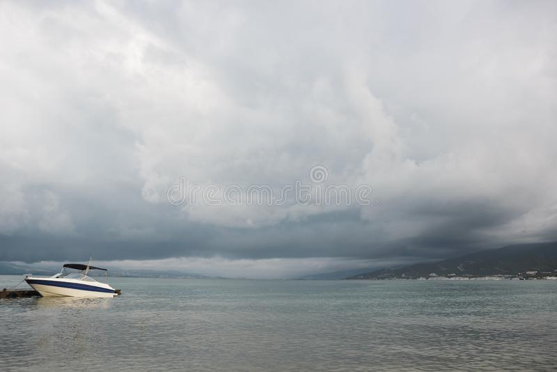 Small sport fishing white boat on approaching storm background royalty free stock image
