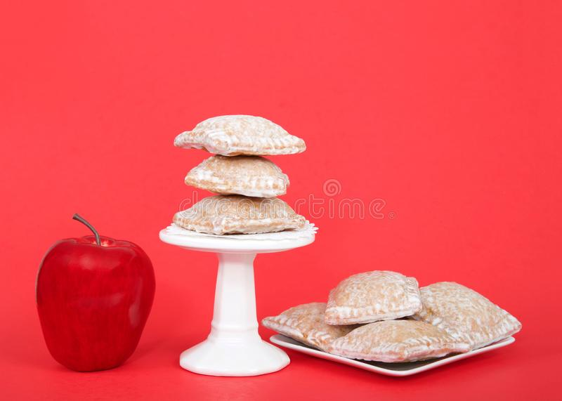 Small square apple pie tarts on a pedestal with more on a plate. Miniature square Apple pie dumplings coated with sugar, sitting on a pedestal and a square white royalty free stock image