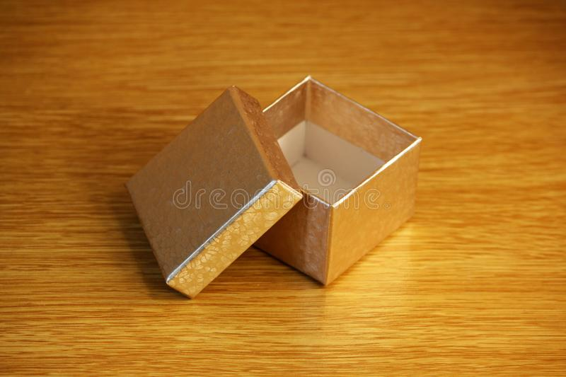 A small square golden box on a light yellow wooden background. soft reflective light. stock photos