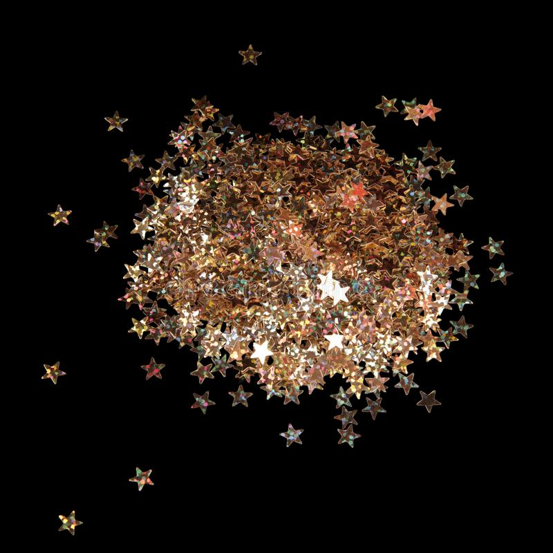 Small stars sparkling brightly isolated on black. Background royalty free stock image