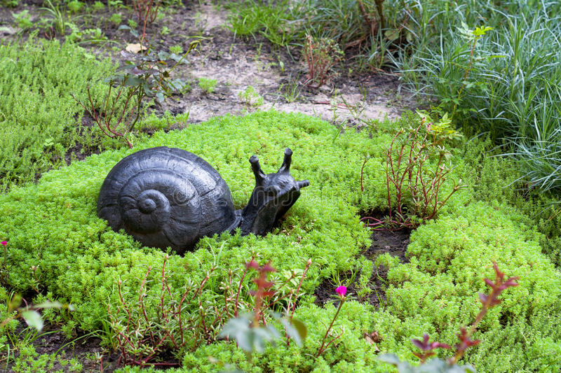 A small statue in the park. Decorative snail in the garden surrounded by green grass and flowers royalty free stock photography