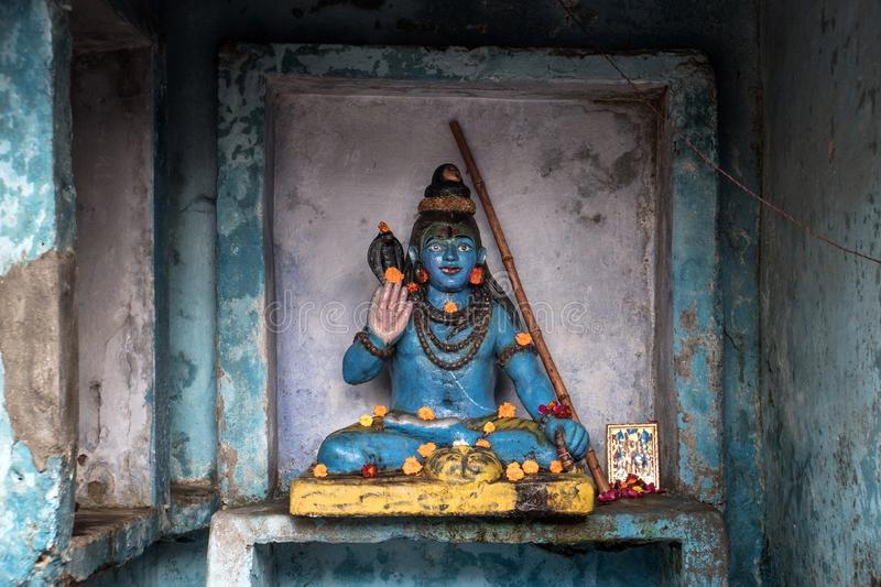 A small statue of Shiva on the background of the blue wall. royalty free stock image