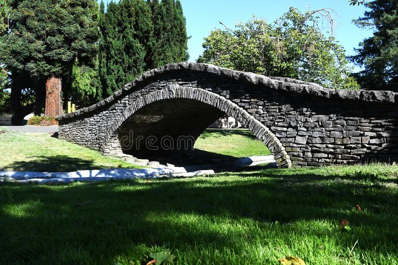 Small Stone viaduct bridge in a local park across small river in Santa Rosa, California. On a summer day stock image