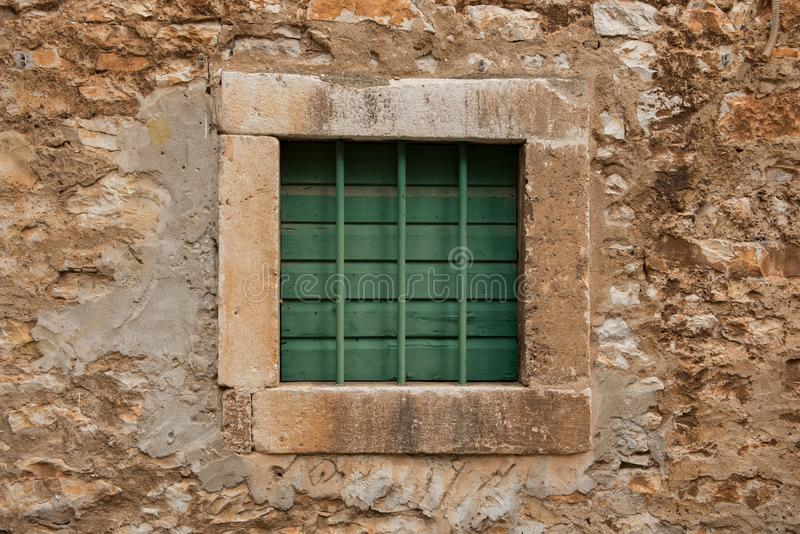 Small stone window closed with green wooden planks and green metal bars. Old style window. Vintage architecture royalty free stock photography
