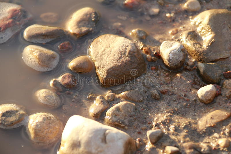 Small stones lying on the ground and in the water and illuminated by the sun stock photo
