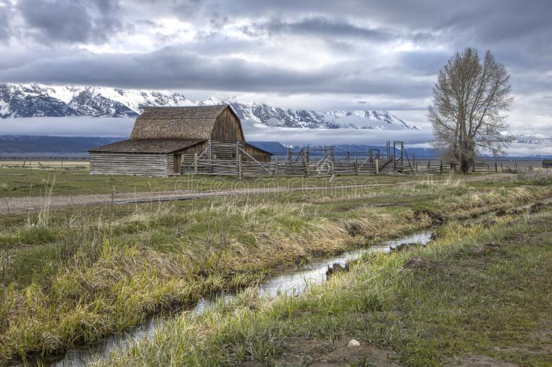Small stream runs by Mormon Row barn. The scenic Moulton barnson mormon row at the Grand Tetons in Wyoming royalty free stock photos