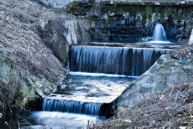 Small stream with waterfalls exiting old dam. Through crack royalty free stock photos