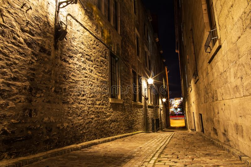 Small street and historical buildings in the historic site of Old Port from Montreal, night view. Scenic background of Canadian stock images