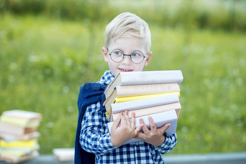 A small strong boy holds a lot of textbooks in his hands. The concept of learning, school, mind, lifestyle and success stock photos