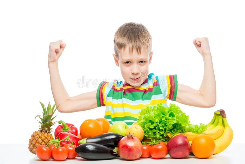 small strongman shows biceps at the table with a pile of fresh vegetables and fruits isolated stock photos