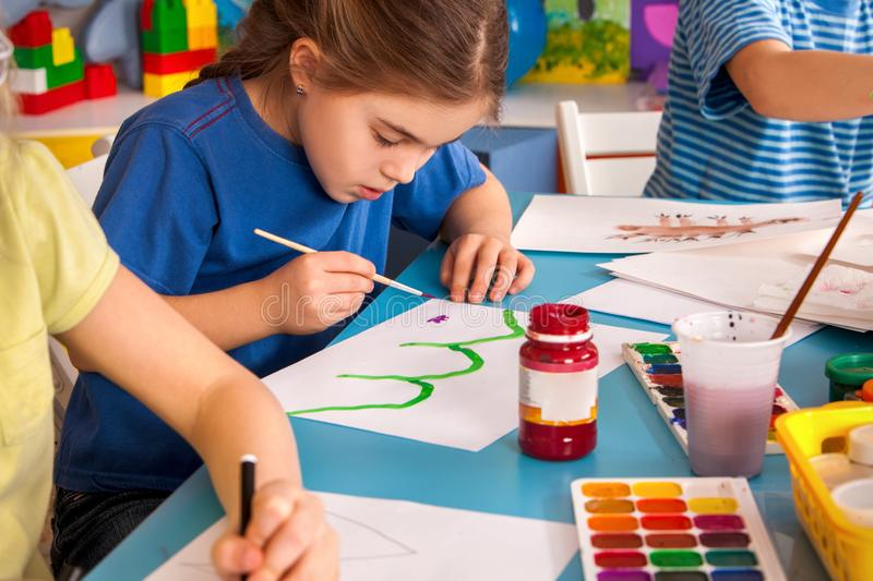 Small students children painting in art school class. Small students painting in art school class. Child drawing by paints on table. Boy and girls in royalty free stock photos
