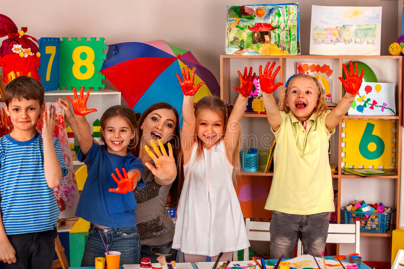 Small students girl finger painting in art school class. Small students with teacher finger painting in art school class. Teacher cheers children in royalty free stock photo