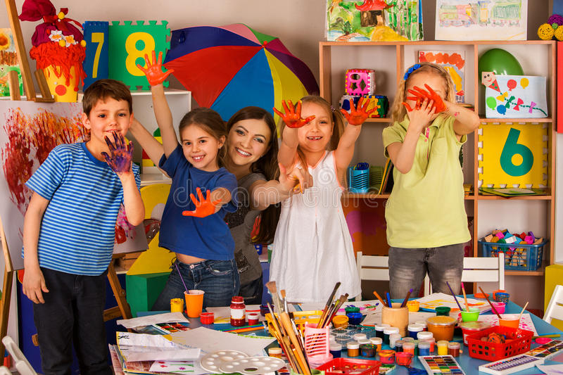 Small students girl finger painting in art school class. Small students with teacher finger painting in art school class. Teacher cheers children in royalty free stock image