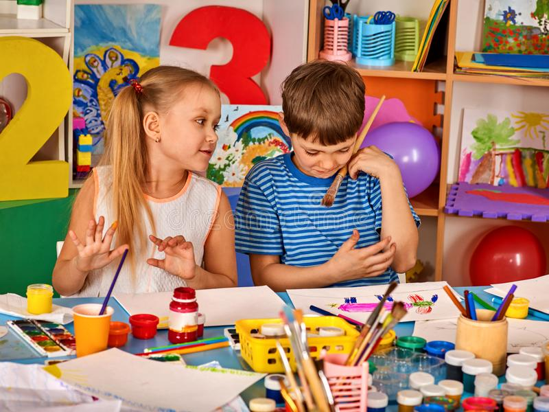 Small students girl painting in art school class. Small students painting in art school class. Children boy and girl drawing by paints on table. Three children stock photography