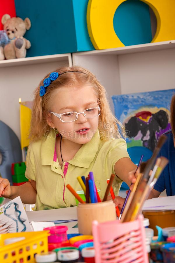 Small students children painting in art school class. Small students painting in art school class. Child drawing by paints on table. Boy and girls in stock image