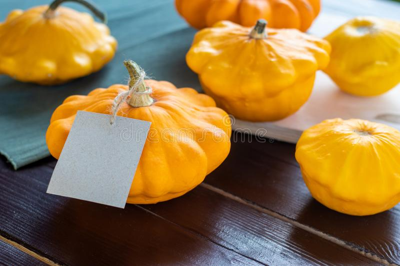 Small summer squash, orange and yellow pumpkins on a wooden table with a craft paper tag, copyspace, autumn farm food. Lots of small summer squash, orange and stock image