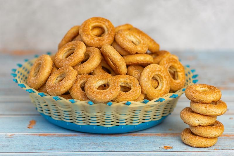 Small sweet bagels in a wicker bowl on light blue wooden background royalty free stock photo