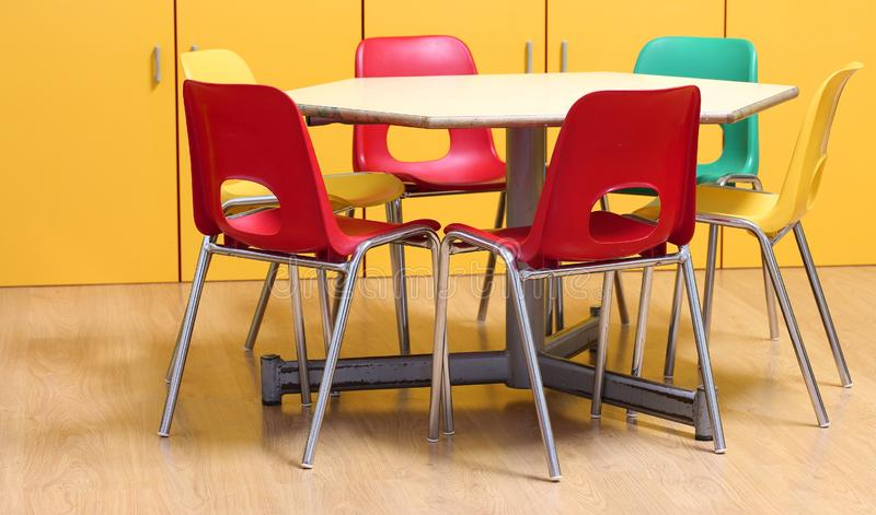small table with colored chairs in the kindergarten classroom stock image