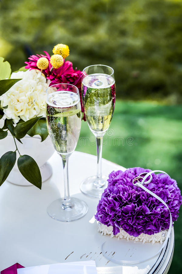 Small table with glasses with champagne and wedding rings royalty free stock photos