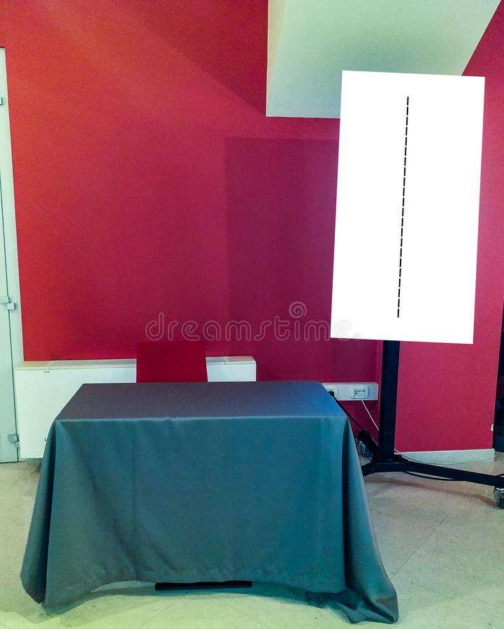 Small table with placemat and chair with a white board at the side. for background a red wall.  royalty free stock photo