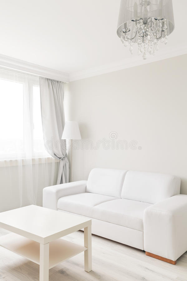 Small table and sofa. Picture of small table and sofa in simply furnished lounge royalty free stock images