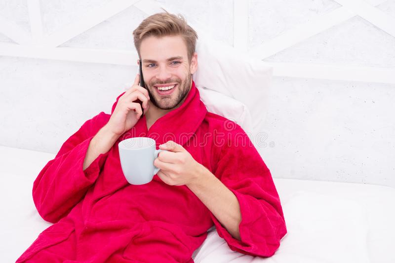 Small talk over his favorite drink. Happy man talking on phone with cup of hot drink in bed. Bearded handsome guy stock photos