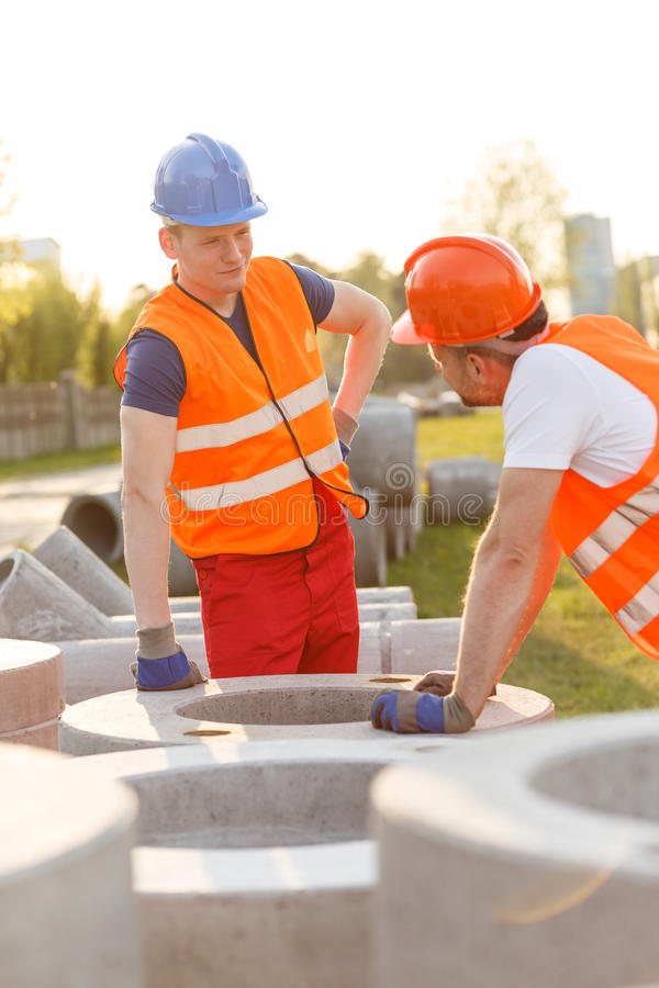 Small talk at work. Tired construction workers having small talk at work royalty free stock images