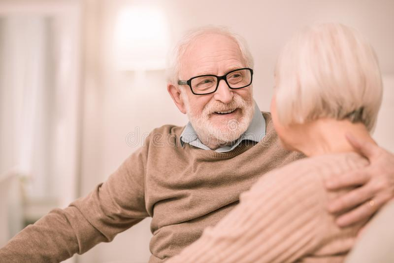 Cheerful pensioner looking into eyes of his wife. Small talks. Kind bearded men expressing positivity while embracing his partner royalty free stock images
