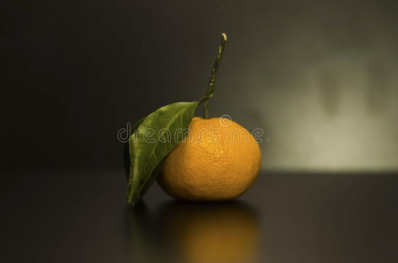 A small Mandarin orange with a leaf. royalty free stock images