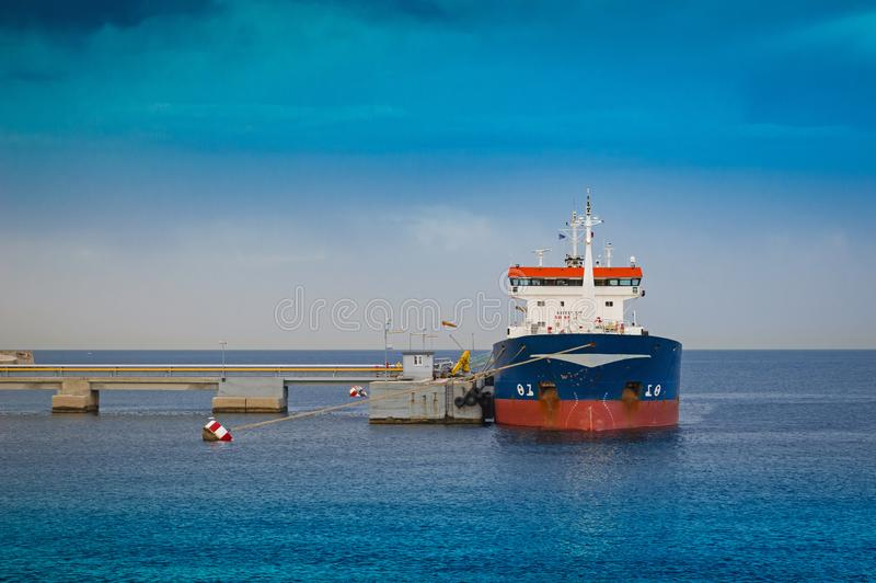 Small tanker ship bringing its cargo in a tank storage facility. View of a small tanker ship bringing its cargo in a tank storage facility, Piraeus - Greece stock photos