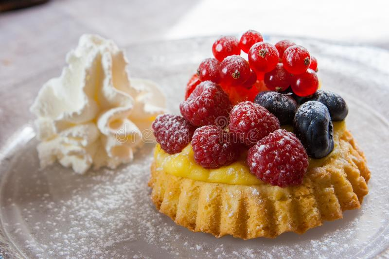 Small tartelette, dessert with blueberries, raspberries and crea royalty free stock images
