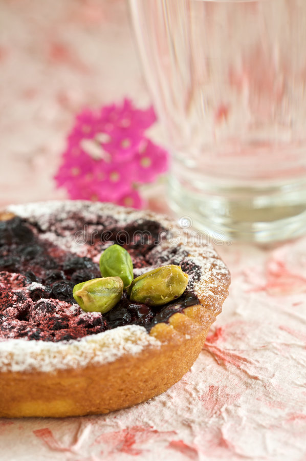 Small tartelette with prunes and pistachio nuts. On colorful background stock photo