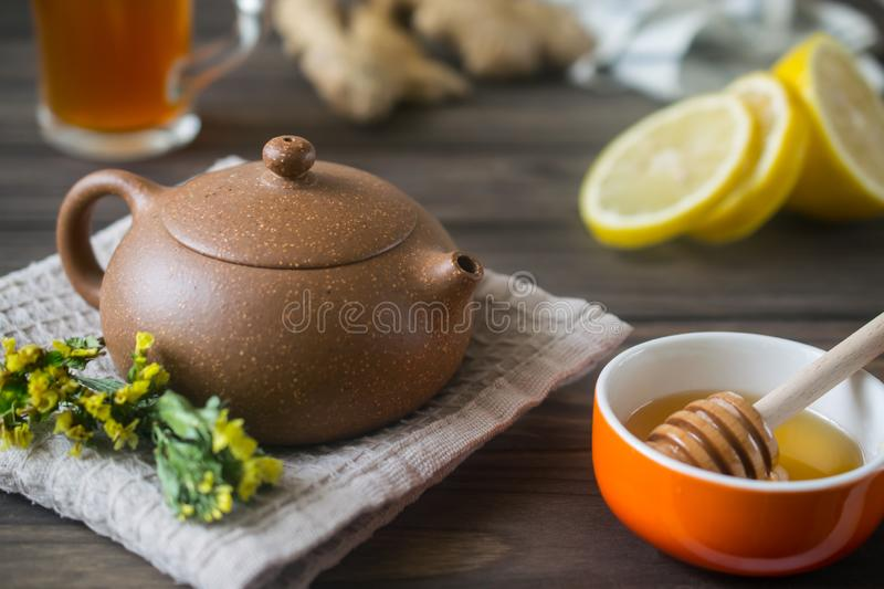 Small teapot with herbal tea on wooden table with lemon and honey stock photo
