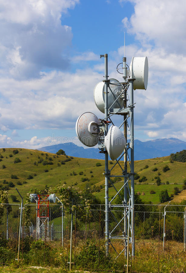 Small telecommunication tower. A closeup of a small telecommunication tower with mountains in the background royalty free stock photo