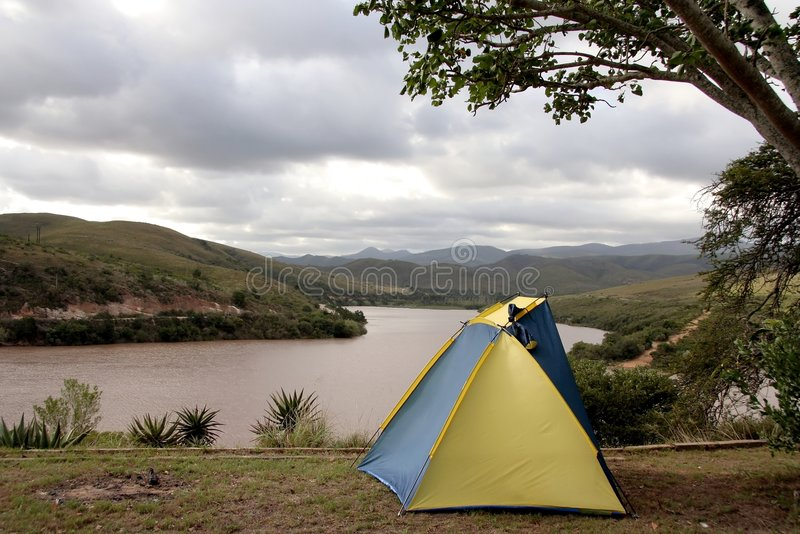 Small Tent at a Dam. Small blue and yellow tent at a camping site next to a dam royalty free stock images
