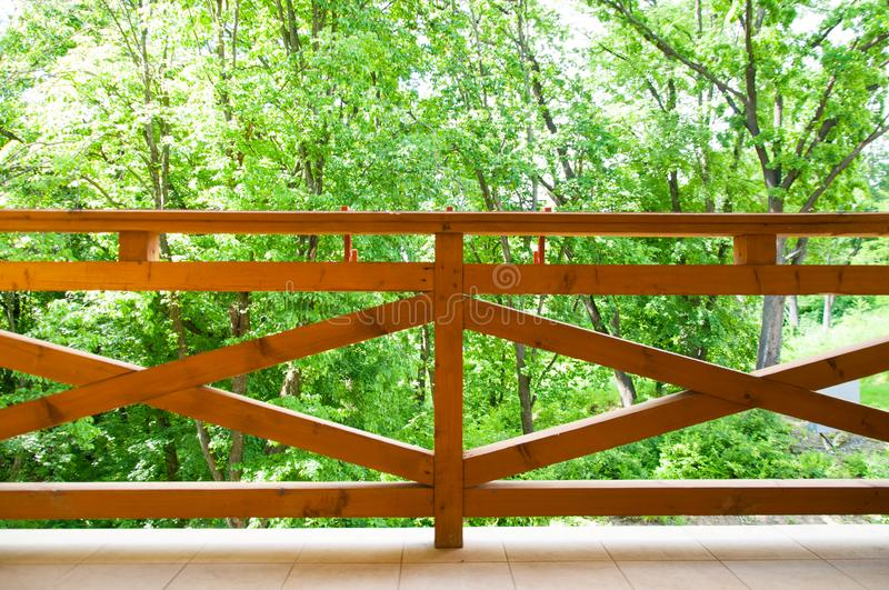 Small terrace with large wooden railing. It`s summer outside. royalty free stock photography