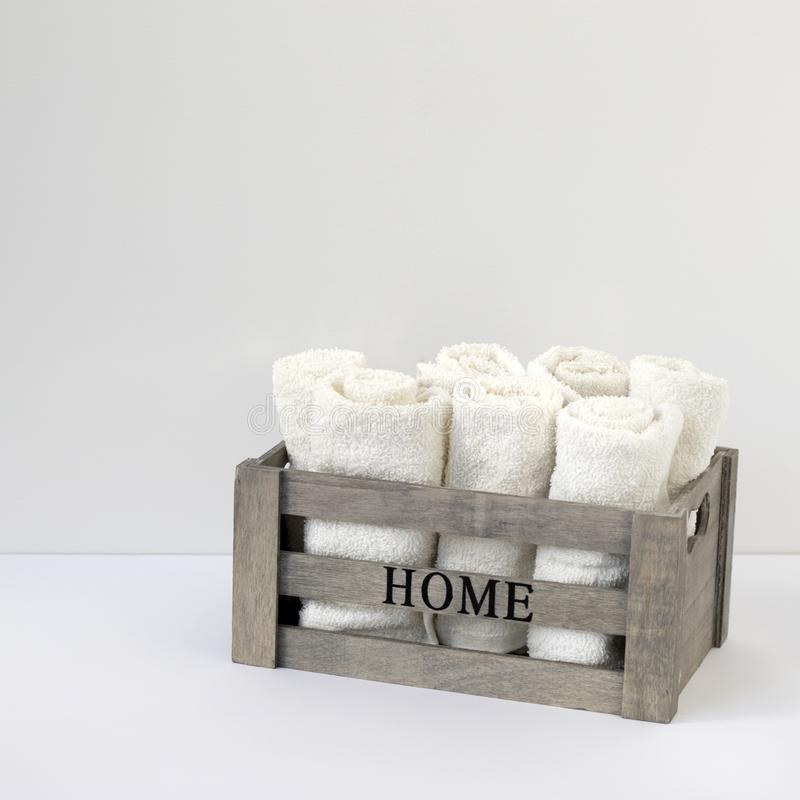 Small terry hand towels rolled into rolls in a wooden box on a window in the bathroom. Copy space stock images