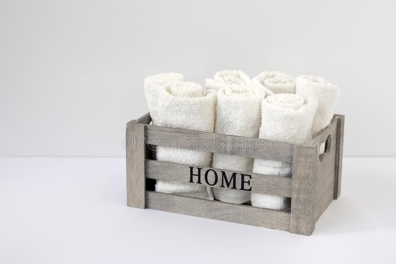 Small terry hand towels rolled into rolls in a wooden box on a window in the bathroom. Copy space stock photo