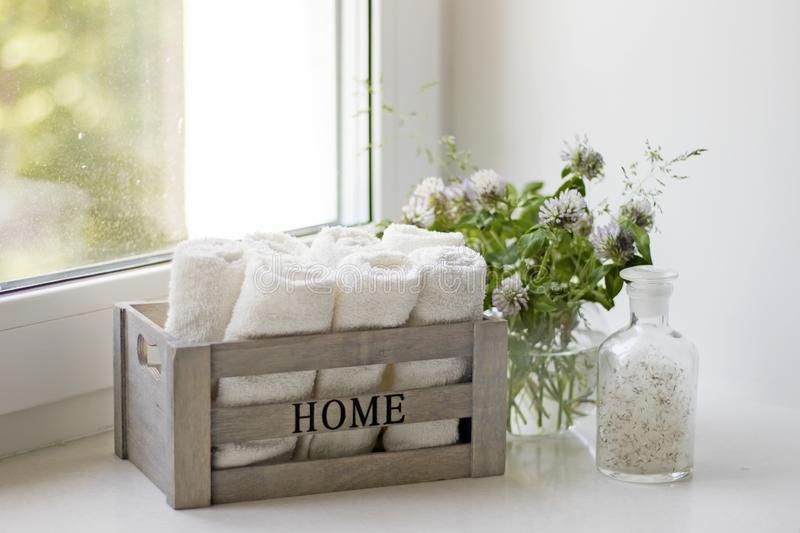 Small terry hand towels rolled into rolls in wooden box on a window in the bathroom. Small terry hand towels rolled into rolls in a wooden box on a window in the stock images